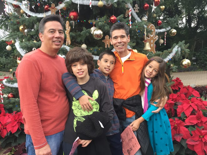 Craig Yabuki, left, celebrates Christmas at the Mitchell Park Domes in 2016 with his twin sons Owen and Grant, brother Jeff, and daughter Lauren.