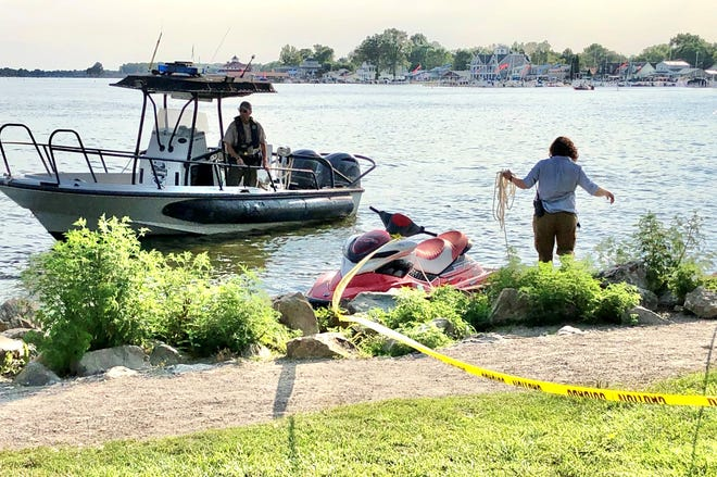 An ODNR officer and investigator inspect a jet ski that was involved Thursday afternoon in a drowning.