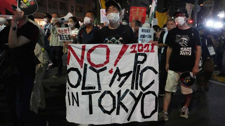 People march in protest during the opening ceremony for the Tokyo Olympics.