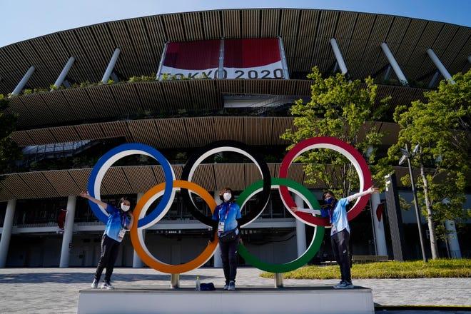 Des bénévoles posent avec les anneaux olympiques lors de la cérémonie d'ouverture des Jeux olympiques d'été de Tokyo 2020 au stade olympique.
