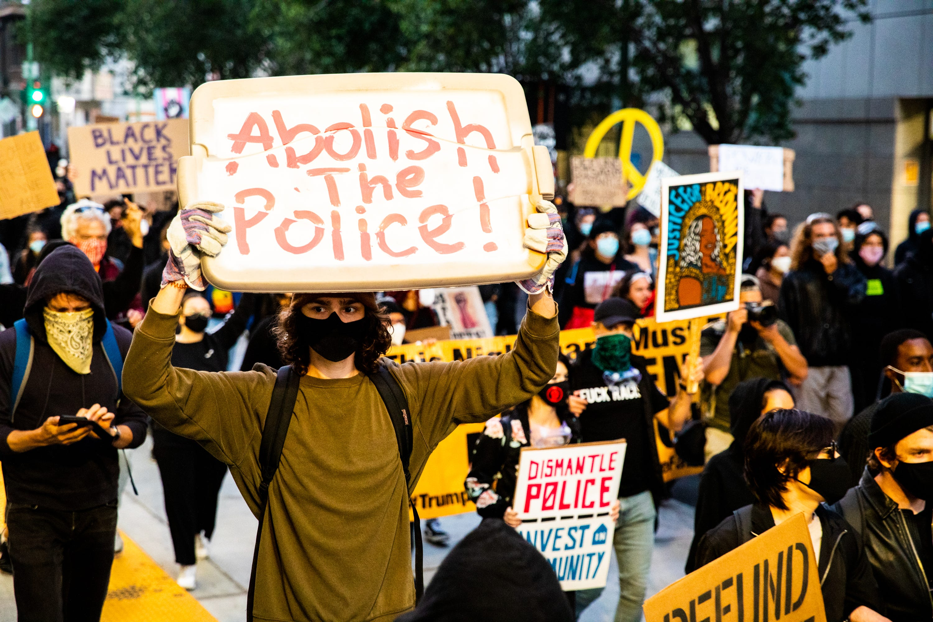 OAKLAND, CALIFORNIA - JULY 25:  Protesters hold signs in support of defunding the police on July 25, 2020 in Oakland, California. Demonstrators in Oakland gathered to protest in solidarity with Portland protests. (Photo by Natasha Moustache/Getty Images)