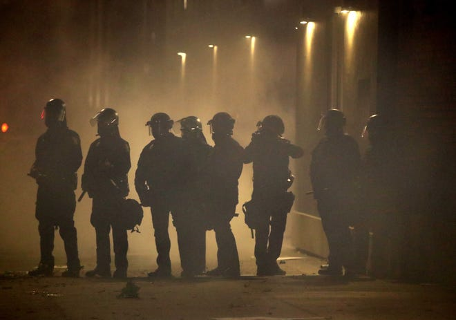 OAKLAND, CALIFORNIA - MAY 29: Police officers stand in a fog of tear gas during a protest sparked by the death of George Floyd while in police custody on May 29, 2020 in Oakland, California. Earlier today, former Minneapolis police officer Derek Chauvin was taken into custody for Floyd's death. Chauvin has been accused of kneeling on Floyd's neck as he pleaded with him about not being able to breathe. Floyd was pronounced dead a short while later. Chauvin and 3 other officers, who were involved in the arrest, were fired from the police department after a video of the arrest was circulated. (Photo by Justin Sullivan/Getty Images)