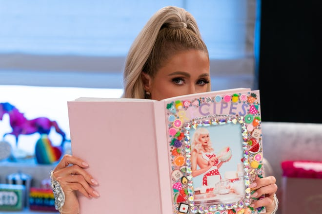 Paris Hilton is learning to cook with a blinged-out recipe book and her celebrity pals.