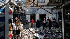 Iraqis inspect the site of an explosion in a market in the Shiite-majority Sadr City neighborhood, east of the capital Baghdad, on July 20. Iraqis mourned at least 36 people killed when a bomb ripped through the market in what Islamic State jihadists claimed was a suicide attack.