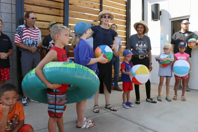 Amarillo Mayor Ginger Nelson and Mayor Pro-Tem Freda Powell stand with kids from the community as Amarillo Parks and Recreation officially opens Thompson Park Pool with a ribbon cutting ceremony Saturday morning.