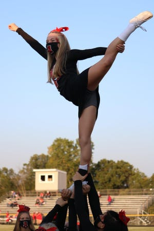 Addison's Emma Spink performs a scale extension stunt during the 2021 sideline cheer season at a football game.