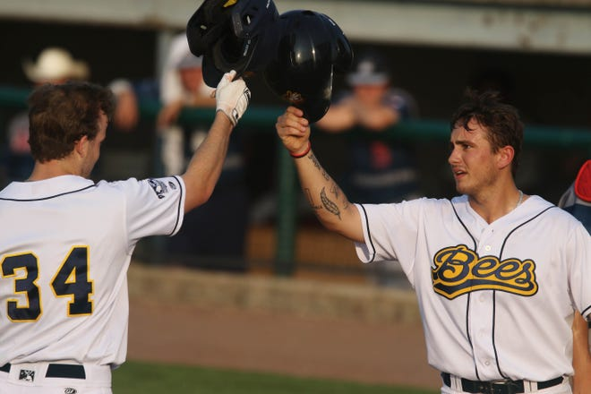 Burlington Bees AJ Henkle (34) is congratulated by teammate Dylan Hale (45) after hitting a two run homer during their game against the Quincey Gems Friday July 23, 2021, at Community Field.