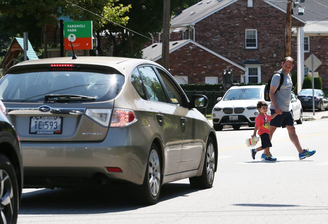 Councilman David Salvatore and son Bennett, 3, walk to Providence's Fargnoli Park on Saturday. Salvatore championed a new ordinance designed to make the city's streets safer for bicyclists, runners and pedestrians.