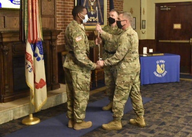 Incoming U.S. Army Chemical, Biological, Radiological and Nuclear School Regimental Chief Warrant Officer 3 Humphrey Hills (left) accepts a sword from Col. Sean Crockett, USACBRNS commandant, as outgoing Regimental Chief Warrant Officer 3 Robert Lockwood looks on during a change-of-responsibility ceremony July 22 at the CBRN Regimental Room in the John B. Mahaffey Museum Complex. Photo by Brian Hill, Fort Leonard Wood Public Affairs Office