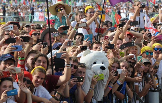 Faithful take photos of Pope Francis as he arrives to celebrate a Holy Mass on the meadows in Brzegi, Poland, on July 31, 2016. The Mass was the final part of the World Youth Day, a global celebration of young Catholics, on the fifth day of the Pope's visit to Poland.