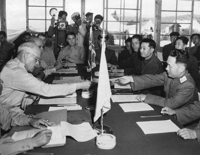 In this July 27, 1953, photo, US Maj. Gen. Blackshear M. Bryan, left, exchanges credentials with North Korean Lt. Gen. Lee Sang Cho at the opening session of the Military Armistice Commission at the Panmunjom Conference House. At Lee's right is Chinese Gen. Ting Kuo Jo, and next to him is Chinese Gen. Tsai Cheng Wen.