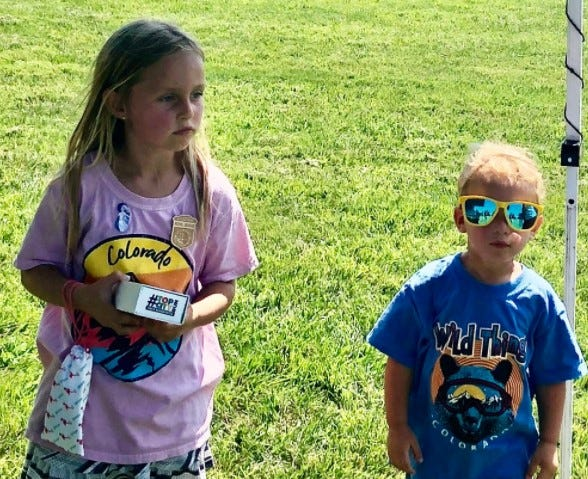Two-year-old Nikolai Hart, on the right, wore a pair of sunglasses Saturday while visiting a vendor's booth and taking part with his 5-year-old sister, Anna Hart, in Family Fun Day activities at Topeka's Central Park.