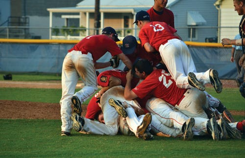 Newburgh celebrates in a pile after winning the 2011 American Legion state championship.