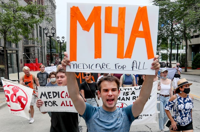 Edward Breihan marches and chants during the Medicare for All march Saturday, July 24, 2021, near East Wisconsin Avenue where they stopped at Sen. Ron Johnson's office in Milwaukee to speak. Behind him others carry signs, including Adelana Akindez, center in black shirt.