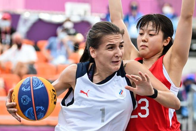 La Russe Yulia Kozik (L) et la Japonaise Mai Yamamoto se battent pour le ballon lors du premier tour féminin de basket-ball 3x3.