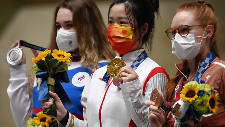 Gold medal winner China's Yang Qian (C) poses on the podium with Russia's Anastasiia Galashina (L) and Switzerland's Nina Christen, after winning the women's 10m air rifle final.