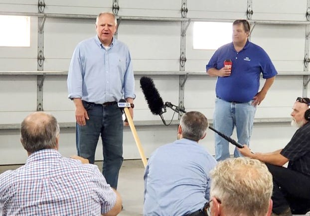 Minnesota Gov. Tim Walz, left, and Minnesota Commissioner of Agriculture Thom Petersen, right, speak at Jim and Robin Reitmeier's rural Crookston farm.