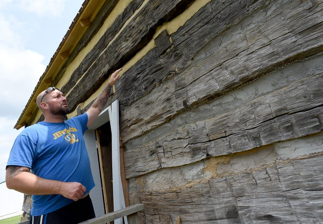 Volunteer Josh McCormick explains how he replaced the mortar between the large wooden beams as part of the restoration of the Eby Log Cabin at the Monroe County Fairgrounds.