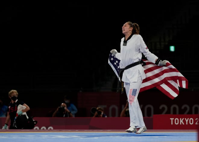 United States' Anastasija Zolotic celebrates as she holds the U.S. flag after winning a gold medal for the taekwondo women's 57kg match at the 2020 Summer Olympics, Sunday, July 25, 2021, in Tokyo, Japan. (AP Photo/Themba Hadebe)