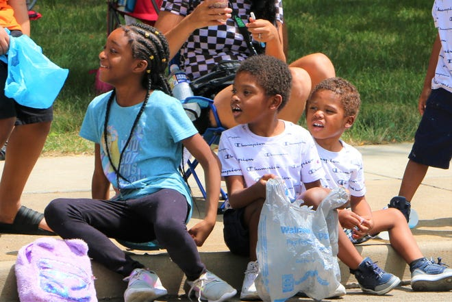 Children watch the Community Parade on Sunday in downtown Canton. The event kicks off the Pro Football Hall of Fame Enshrinement Festival.
