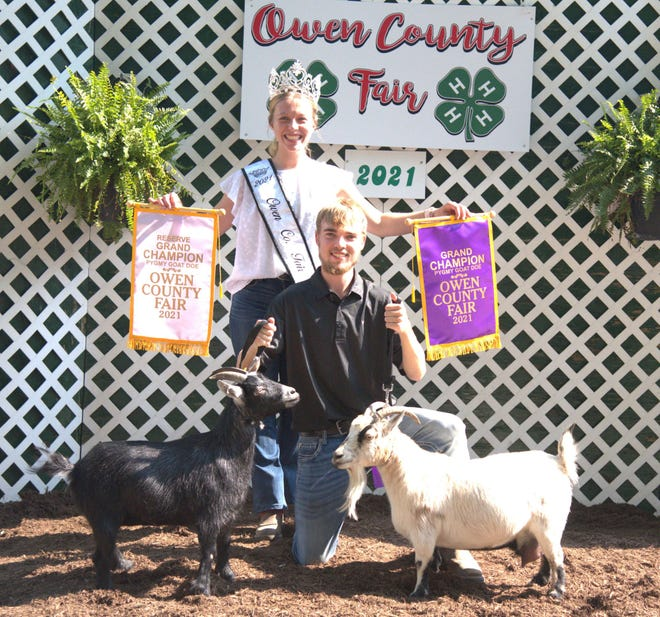Cody Morris poses with his grand and reserve grand champion does after the pygmy goat show while 2021 Owen County Fair Queen Elizabeth Beeman holds his banners.