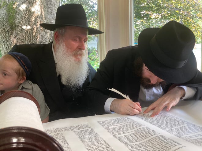 """Rabbi Yitzchok Raskin of Brooklyn, New York, right, writes the last letter of the Torah during Sunday's """"siyum Torah"""" or a completion of the Torah ceremony at the Chabad of Springfield. At left is Rabbi Eli Turen, the father of Rabbi Mendy Turen of Springfield, who started the Chabad community here in 2016. The Torah scroll was then carried to Chabad's new synagogue on South MacArthur Boulevard."""