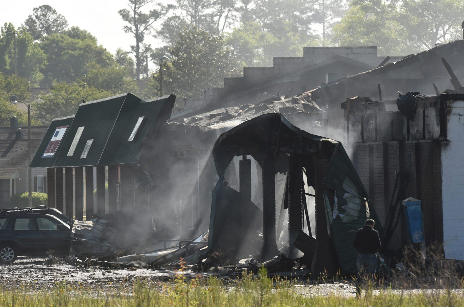 Wilmington Fire Department crews continue to look after the fire at Everybody's Supermarket, along Greenfield St. Thursday May 3, 2018 in Wilmington, N.C. The fire destroyed Village Plaza Shopping Center that included stores like Spiro's Breakfast and Lunch House and Quail's Quality Cuts.