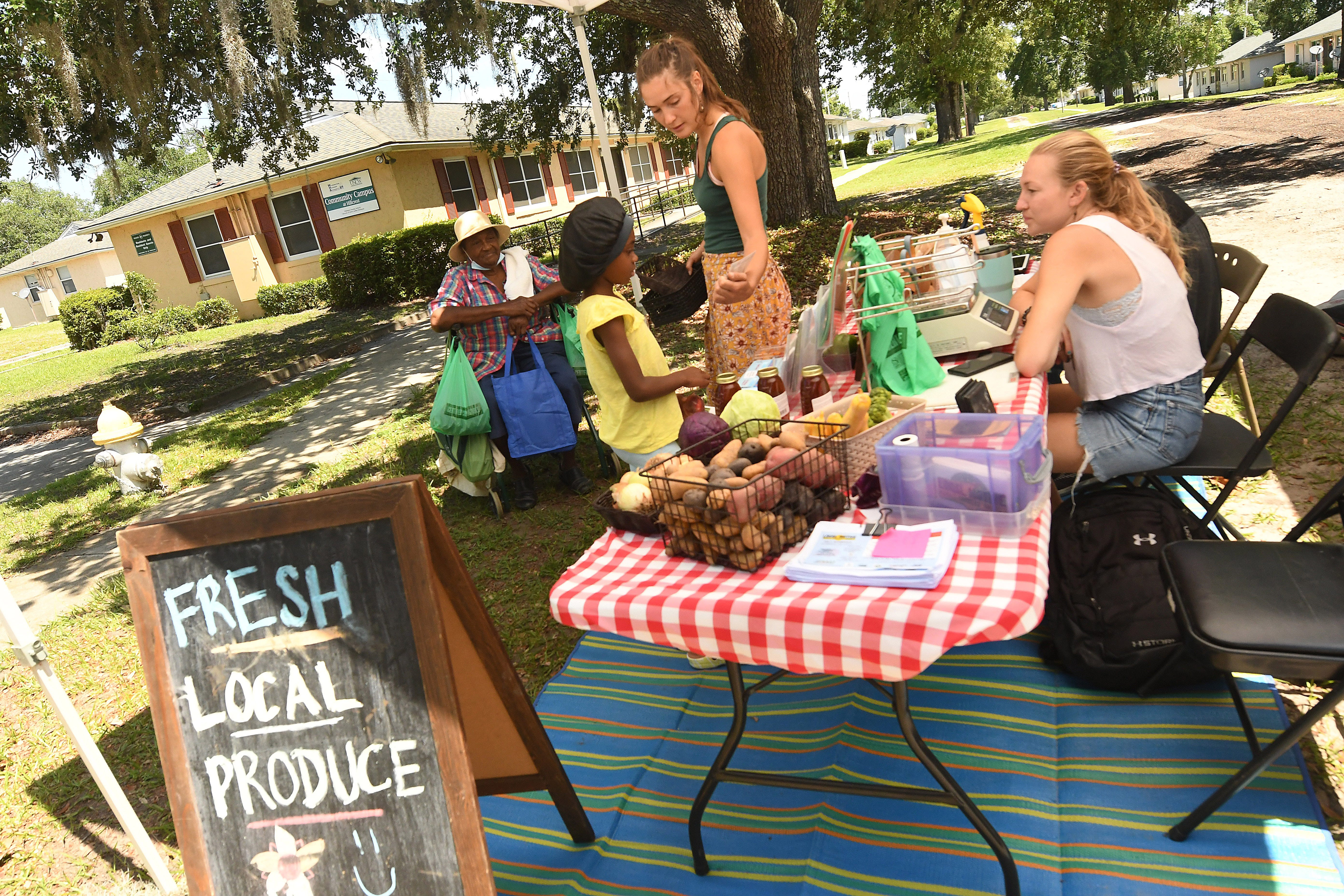Clarisse Owens shares recipes with her customers as she and Alyssa Wood sell fresh produce in the Hillcrest community in Wilmington, N.C.