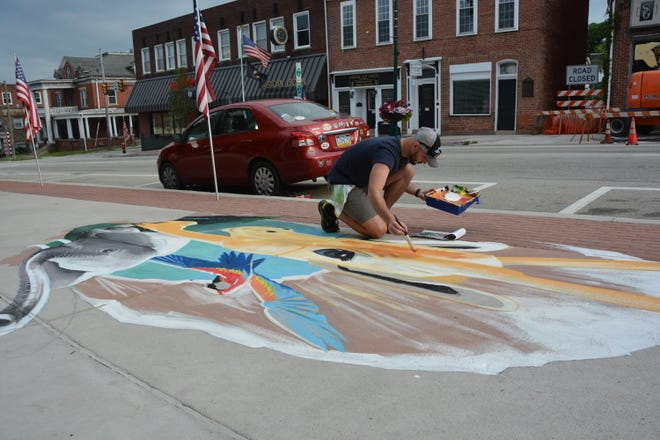 Jesse LuBera of Catasauqua painting a jungle-themed piece in front of Somerset Trust Co. on Sunday morning.