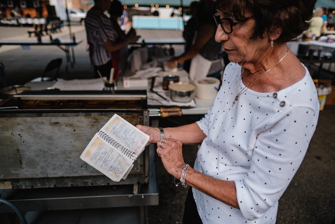 Marlene Ridgway shows a books detailing notes about previous years of frying waffles and dough during the annual St. Mary's Festival, in Dennison, Saturday.