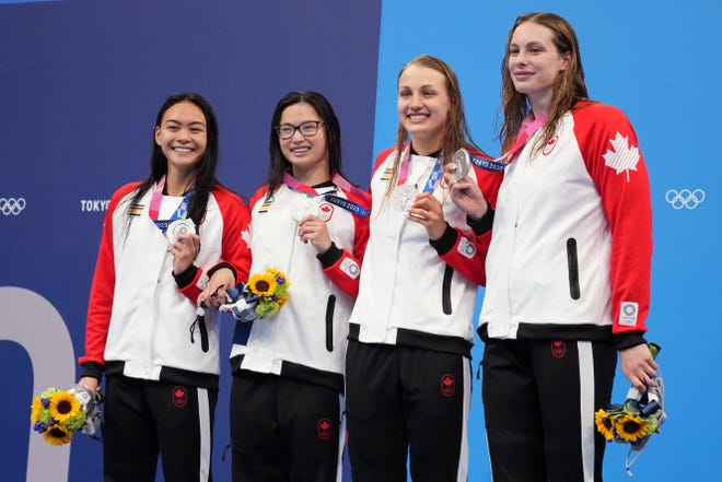 Silver medalists from Canada's women's 4x100 freestyle relay team Kayla Sanchez, Margaret MacNeil (University of Michigan), Rebecca Smith and Penny Olesiak celebrate on the podium as at the 2020 Summer Olympics, Sunday in Tokyo, Japan.