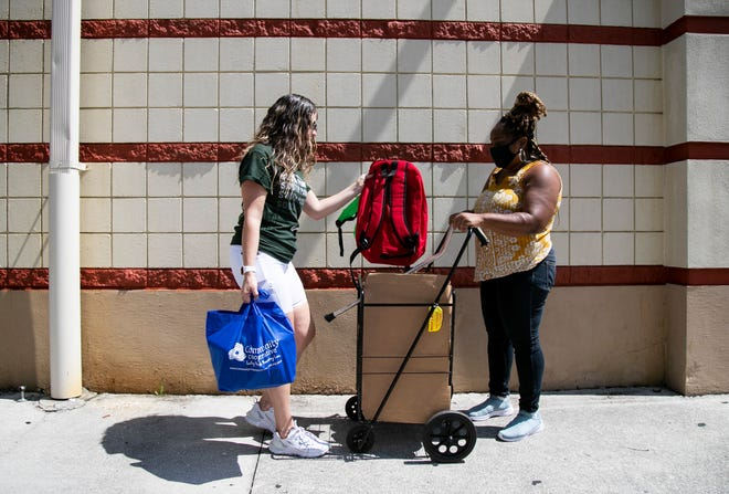 Tae Washington, right, picks up backpacks from volunteer Alyssa Maldonado at the BIG Backpack Event hosted by The Multicultural Centre of SWFL in Fort Myers on Sunday, July 25, 2021.