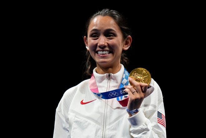 Gold medalist Lee Kiefer of the United States, holds her gold medal during the medal ceremony for the women's individual Foil final competition at the 2020 Summer Olympics, Sunday, July 25, 2021, in Chiba, Japan. (AP Photo/Hassan Ammar)
