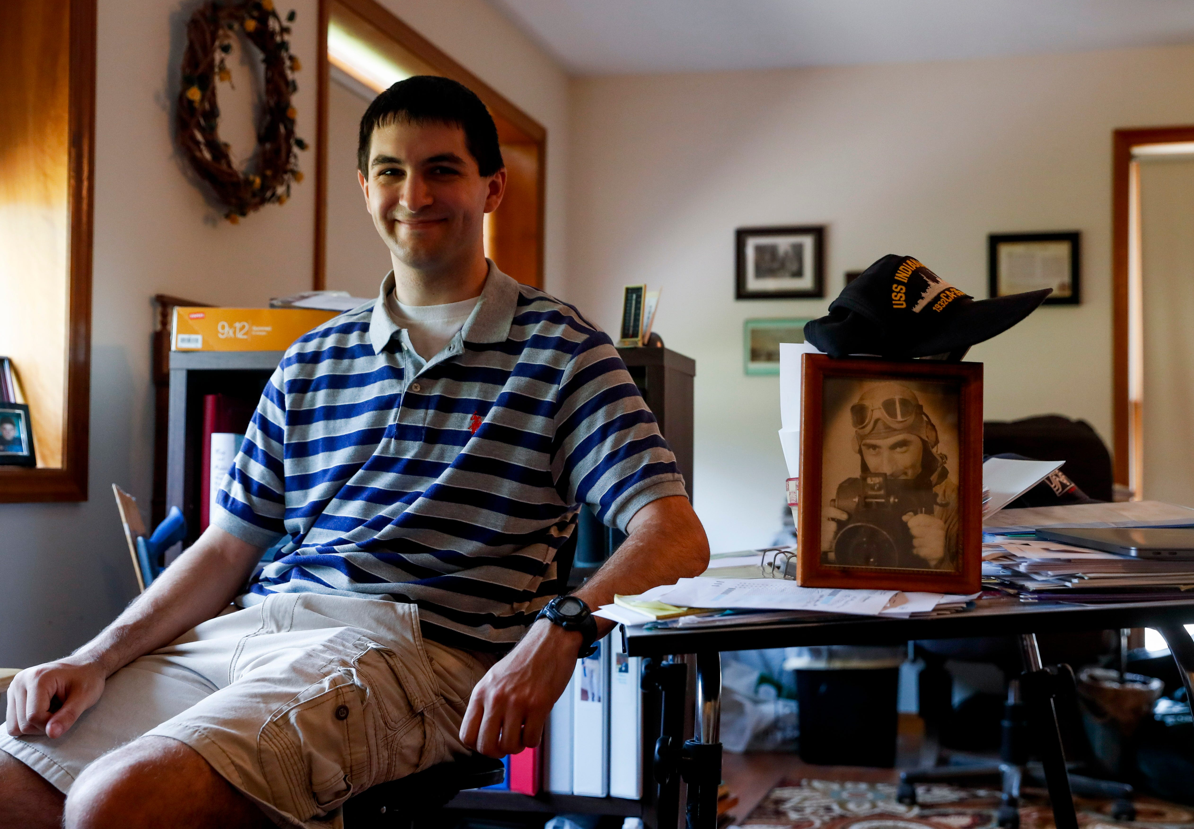 Andrew Triplett sits down for a portrait with a photograph of his great uncle Alfred Sevidi, a photographers mate first class stationed on the USS Indianapolis, at the Lancaster home in Hermitage on July 24.