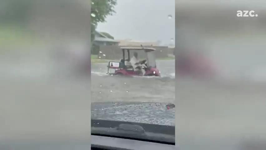 Person drives golf cart through flooding in Sun City