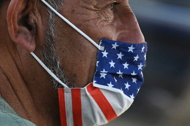 A man wears a U.S. flag face mask on July 19, 2021, on a street in Hollywood, on the second day of the return of the indoor mask mandate in Los Angeles County due to a spike in coronavirus cases. (Robyn Beck/AFP/Getty Images/TNS)