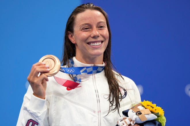 Hali Flickinger holds up her bronze medal for the women's 400-meter Individual medley at the 2020 Summer Olympics, Sunday, July 25, 2021, in Tokyo, Japan. (AP Photo/Matthias Schrader)