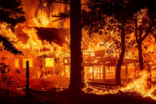 Flames from the Dixie Fire consume a home in the Indian Falls community of Plumas County, Saturday, July 24, 2021. The fire destroyed multiple residences as it tore through the area. (AP Photo/Noah Berger)