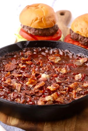 Smoked baked beans cook for at least an hour on your smoker and then are topped with chopped bacon.