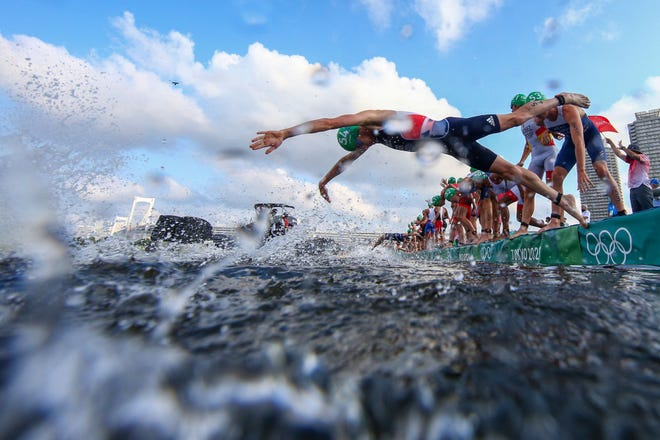 Some athletes dive into the water while others are blocked by a broadcast boat in the men's individual triathlon competition during the Tokyo 2020 Olympic Games.