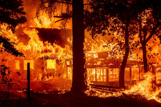 Les flammes de l'incendie de Dixie consument une maison dans la communauté d'Indian Falls du comté de Plumas, en Californie, le samedi 24 juillet 2021. L'incendie a détruit plusieurs résidences alors qu'il dévastait la région.