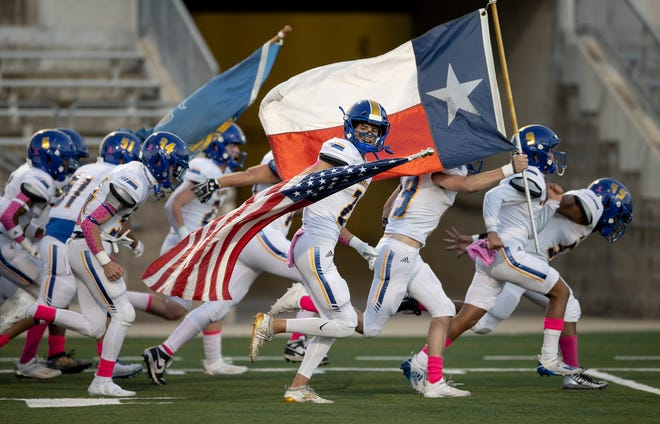 The Austin school district has decided that home-schooled students won't be able to participate in AISD UIL-sponsored events this school year. In this photo, Anderson football player Patrick Winn carries the U.S. flag before a game last fall against Cedar Ridge.