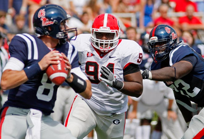 Georgia defensive end DeAngelo Tyson (94) runs past Mississippi offensive linesman Aaron Morris (72) as he rushes Mississippi quarterback Zack Stoudt (8) in the first quarter of an NCAA college football game at Vaught-Hemingway Stadium, Saturday, Sept. 24, 2011, in Oxford, Miss. Stoudt was sacked and Georgia won 27-13. (AP Photo/Rogelio V. Solis)
