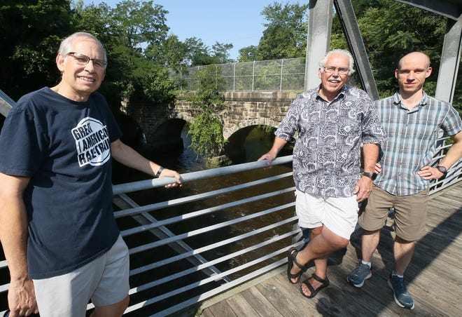 From left, Bill Sepe, Ron Brubaker and Austen Rau of TASCforce, stand on a pedestrian bridge in Cuyahoga Falls as they talk about the stone train bridge crossing the Cuyahoga River along a rail line the group wants to convert to a hike-and-bike trail.