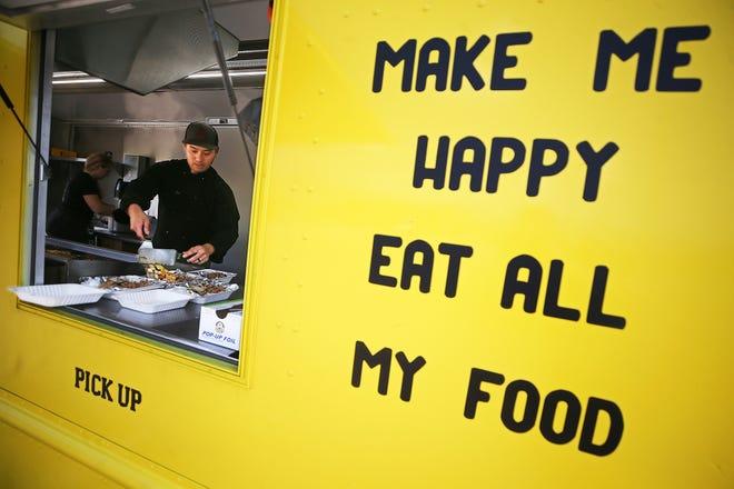 Kitsada Hongsakrai, owner of the Dr. Hibachi food truck, fills orders for customers last week in Cuyahoga Falls.