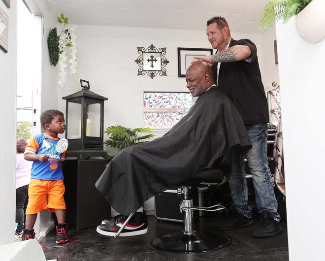 Joshua Hahn, right, cuts the hair of Kevin Smith Sr. as Smith's great-nephew Zion Smith, 4, watches July 24 at an event at OPEN M in Akron. Hahn has converted a camping trailer into a mobile barber shop as part of his Christ N Cuts ministry.