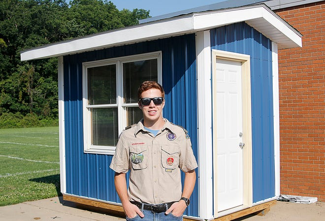 Hillsdale High School graduate Caleb Murawski poses on Monday, July 26 in front of his Eagle Scout project, a ticket booth for the new football stadium at Hillsdale High School that opens this coming season.