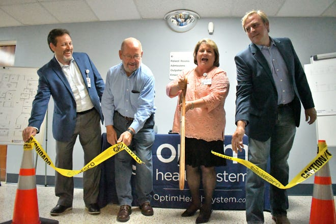 Symbolizing the construction work is to begin, Lagina Evans, the Optim Medical Center -- Screven, cuts the yellow caution tape during a July 20 ceremony at the hospital. Holding the ribbon for the scissors of the Screven County Chamber of Commerce to slice through are Optim CEO David Perry; Hospital Authority Chairman David Boddiford; and County Commission Chairman Will Boyd.