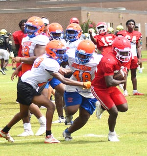 Sophomore Gamecock running back Isaiah Chappel evades the grasps of Johnson High School defenders during the July 21 padded camp at Screven County High School.