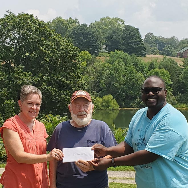 Olney Friends School in Barnesville received $23,000 from Stillwater Monthly Meeting, a part of Ohio Yearly Meeting (Conservative). The money will be used toward  the re-pavement of the Olney driveway. The driveway is estimated to cost $68,000. Bob Rockwell, from the class of 1956 and a member of Stillwater, is presenting the checkto Christian Acedmah, 2001 class member and head of school, and Ann Marie Taber,from the class of '79 and development director, at the school.Olney Friends School, a co-educational boarding and day school affiliated with the Religious Society of Friends (Quakers), opened in 1837 in Mount Pleasant and relocated to Barnesville in 1876. The campus, along with the Stillwater Meeting House are listed on the National Register of Historic Places.